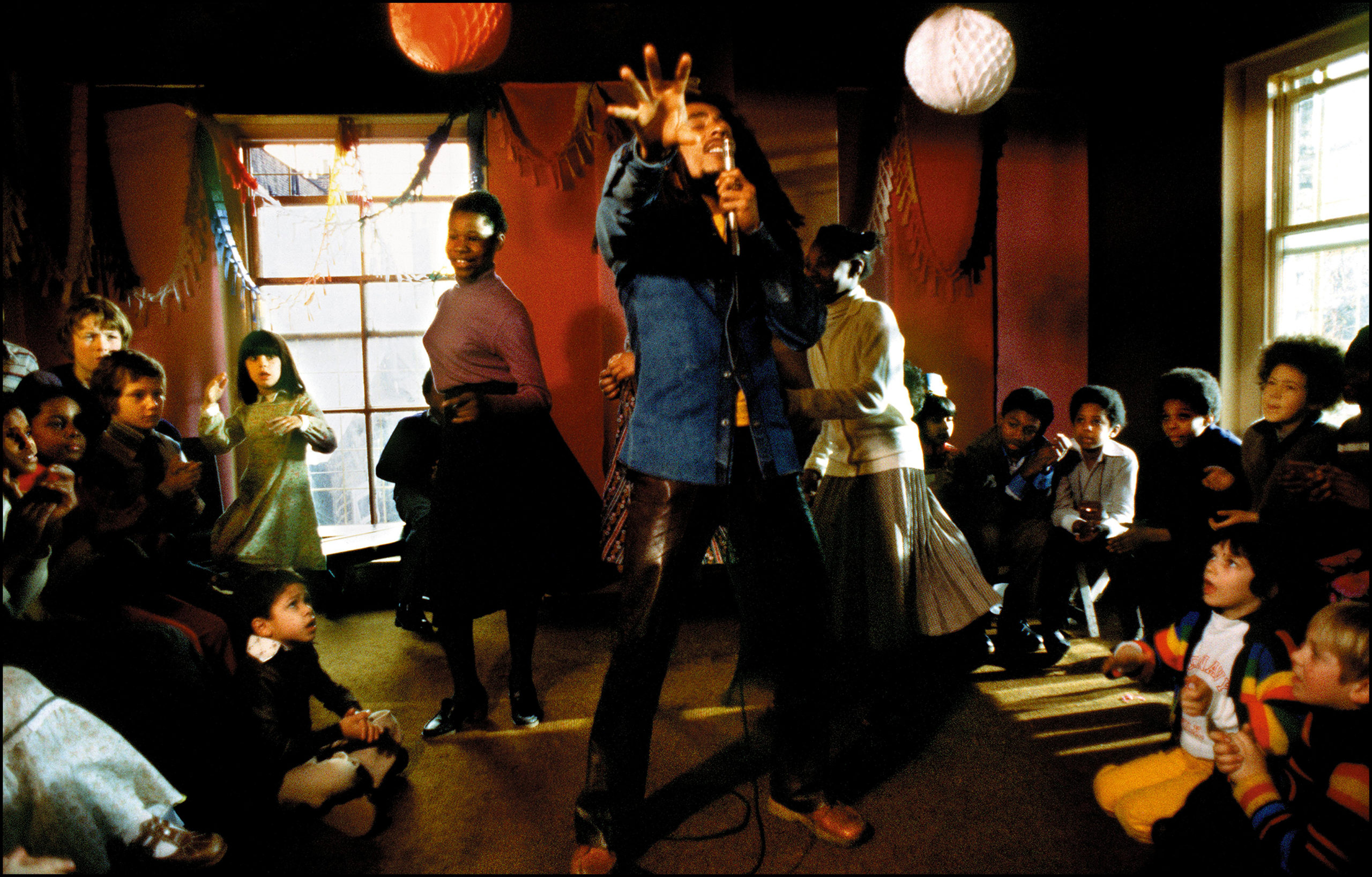 Bob Marley sings into a microphone as two girls dance behind him and children sit and watch.