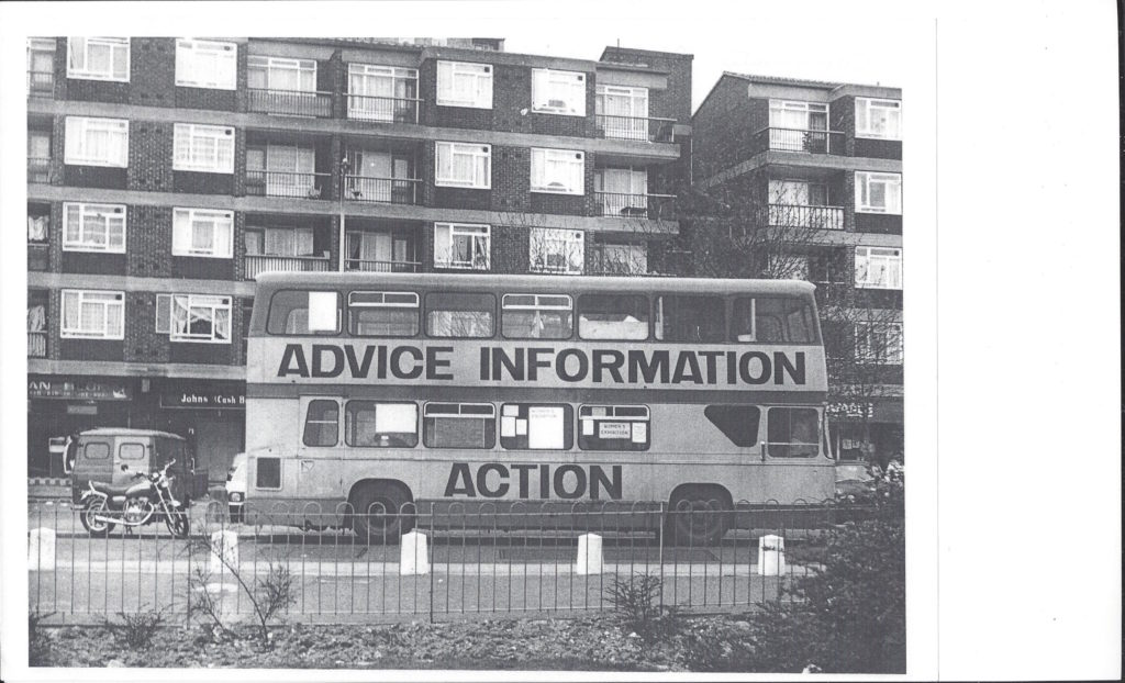 The side of a double decker bus is inscribed with the words 'Advice Information Action'. The bus is parked in front of a block of flats.