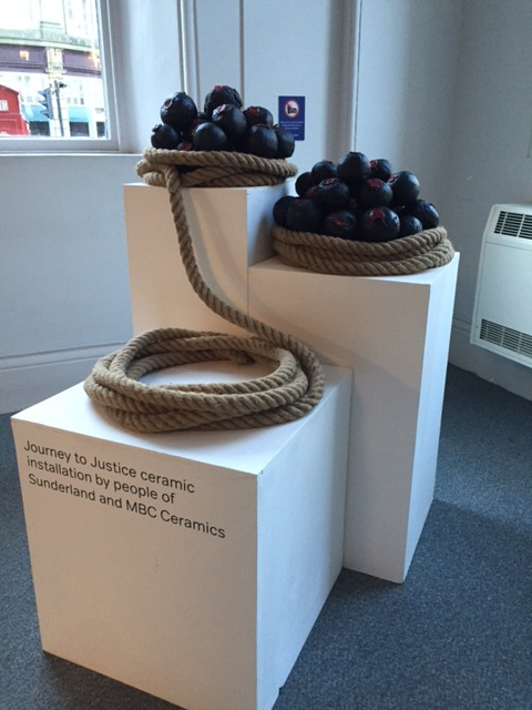Three large white blocks hold an installation of coiled rope. The coils of rope are filled with black cannonballs