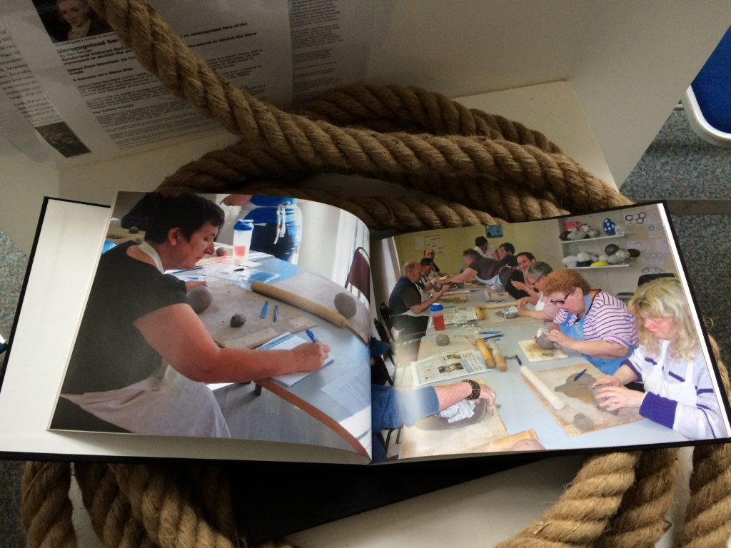 A book lies open on top of a coil of rope. The books shows pictures of people participating in a cannonball making workshop.