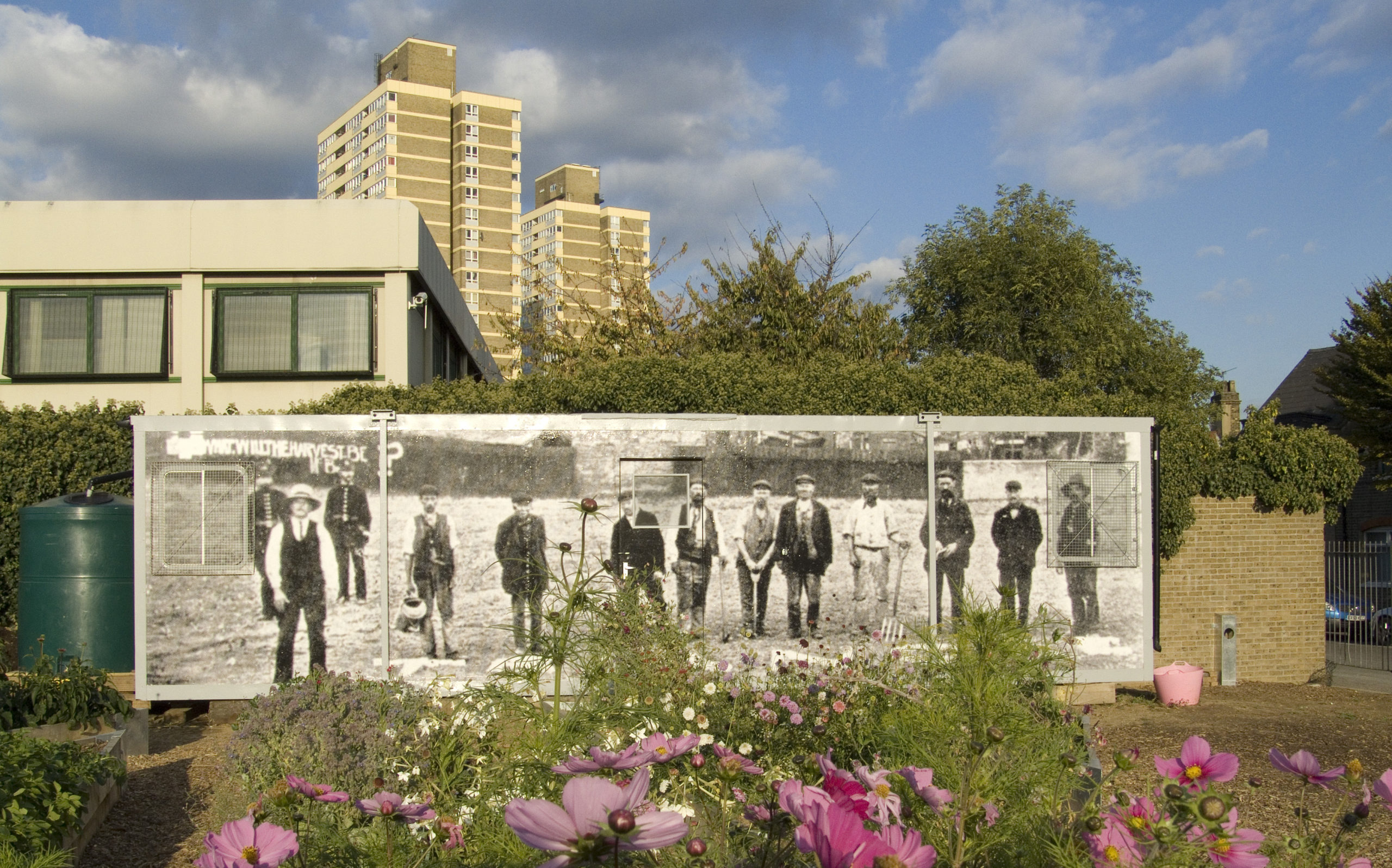 A portacabin stands in the foreground, behind which is a high rise building and a series of trees. A large photographic image covers the wall of the portacabin, depicting the Plaistow land grabbers in their Victorian clothing.