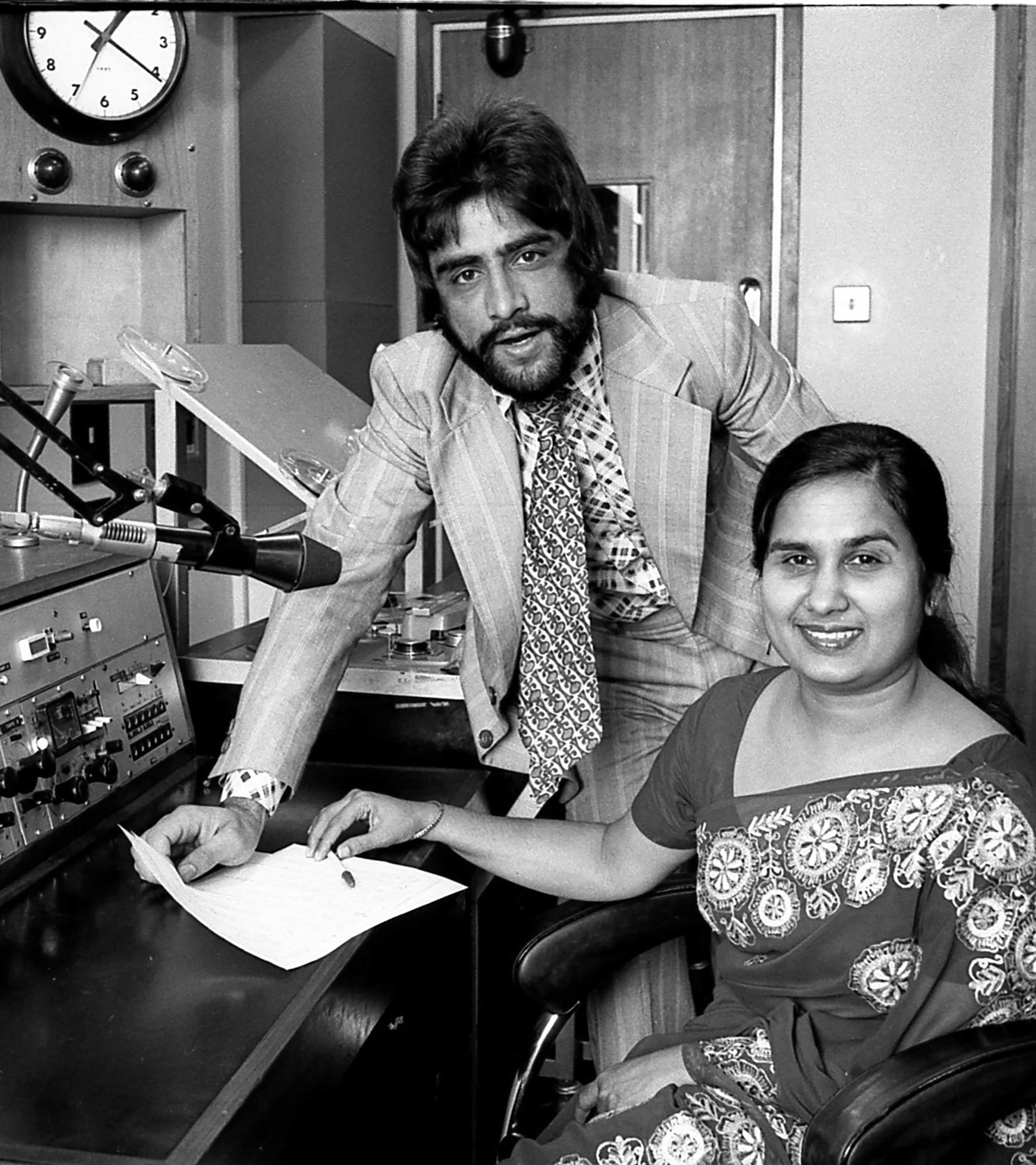Black and white photograph of a bearded Asian man in suit and tie leaning on a desk next to a seated Asian woman in a sari, in a recording studio in front of a microphone and radio equipment.