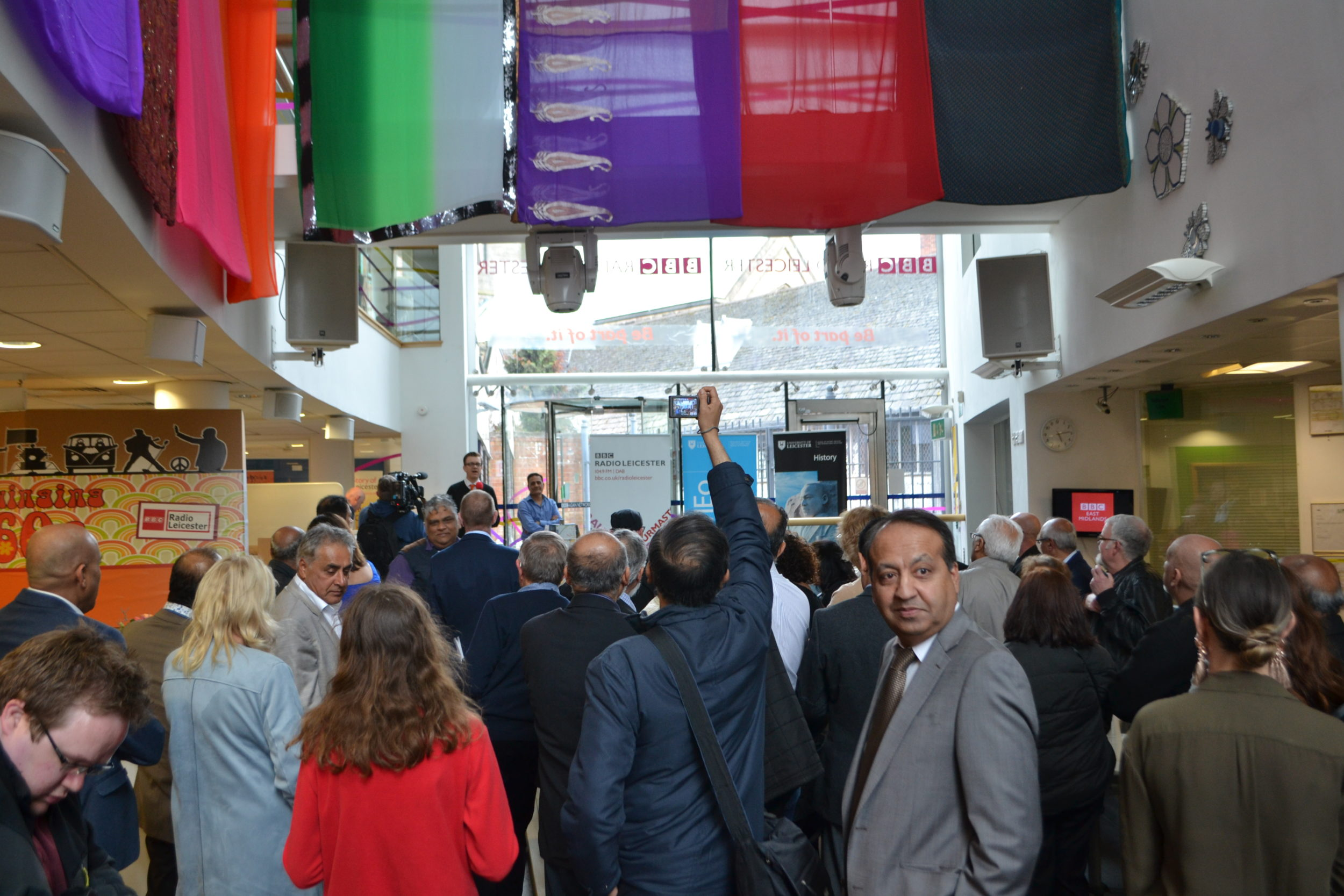 A colour photograph of a gathering of people in the foyer of BBC Radio Leicester.
