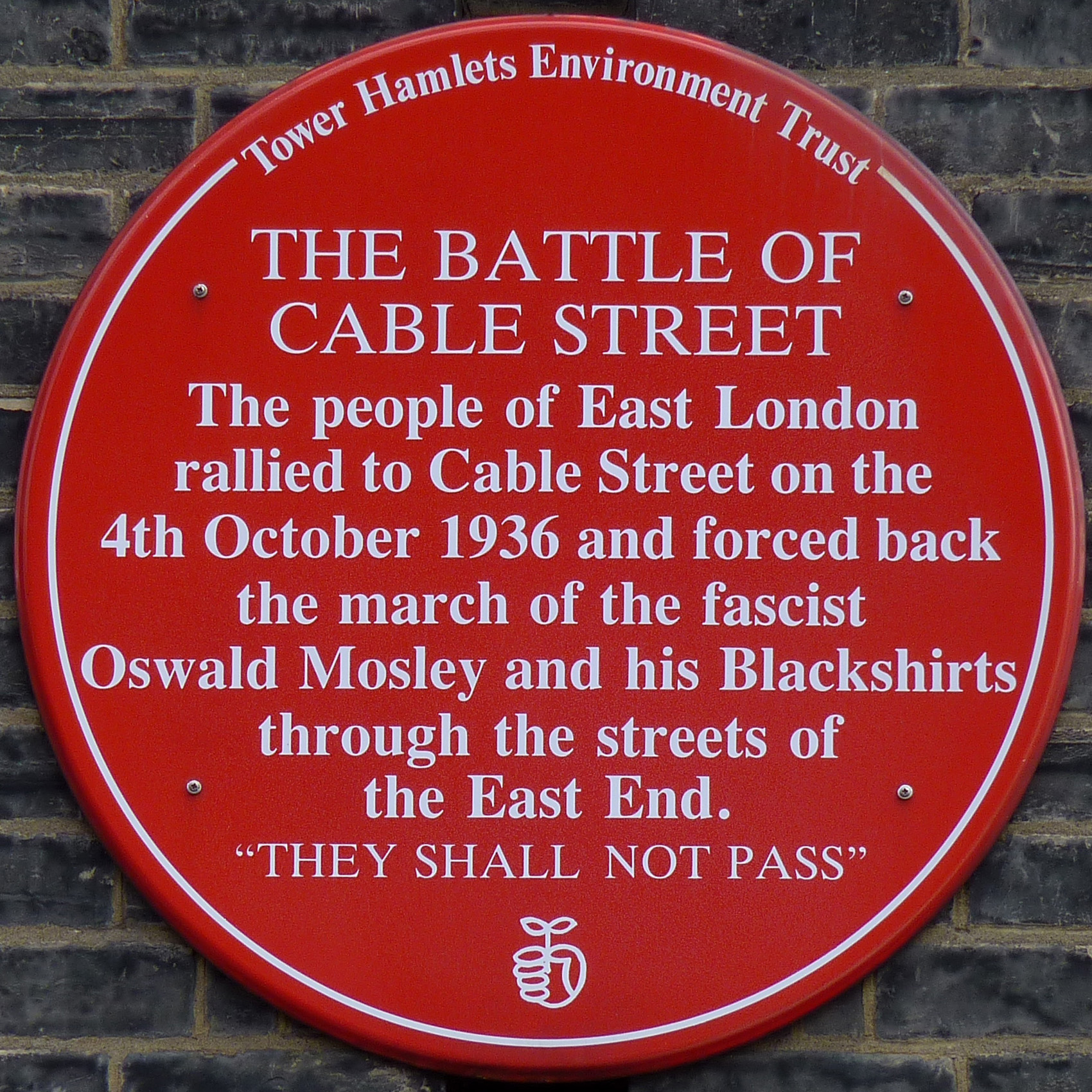 """A circular plaque, white text on red background which reads: """"The people of East London rallied to Cable Street on the 4th October 1936 and forced back the march of the fascist Oswald Mosley and his Blackshirts through the streets of the East End. """"THEY SHALL NOT PASS"""""""