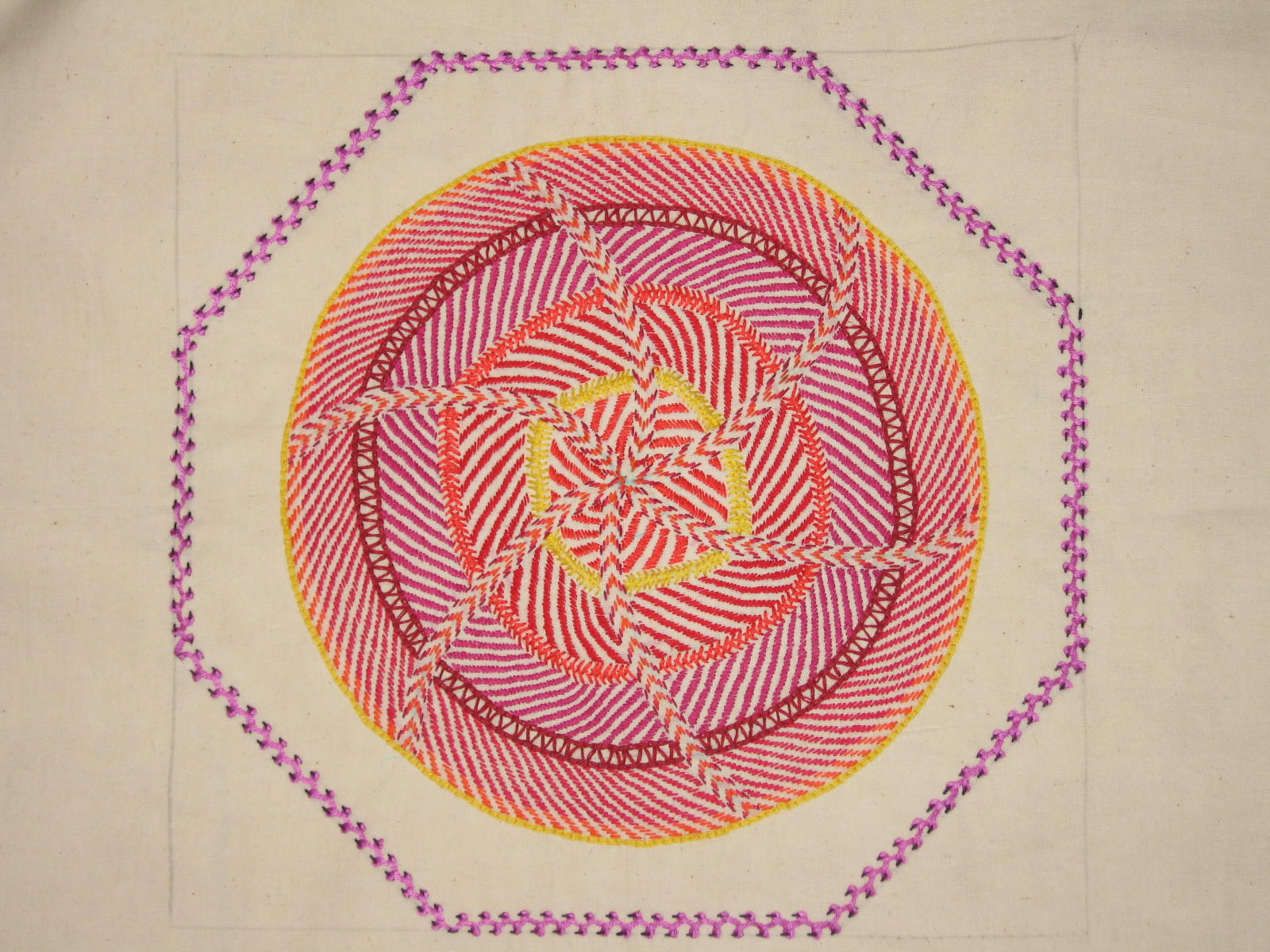 A white material background with purple, red, burgundy, organe and yellow embroidery stitches forming a series of concentric circles in the centre.