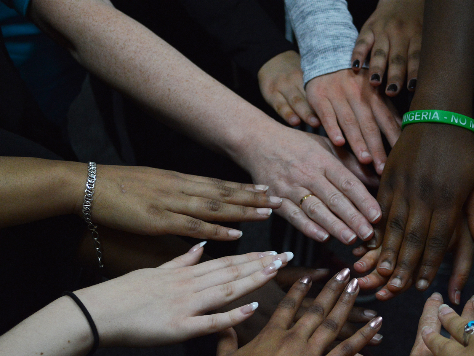 Nine girls' hands are shown – white, black and brown skinned - coming together in a circle.