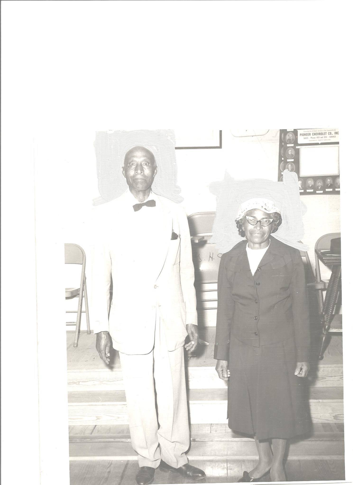 Black and white photograph showing a Black man and woman stood facing the camera.