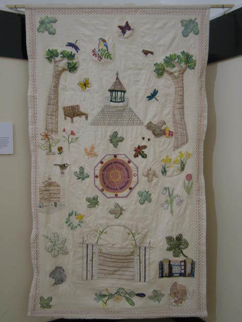 An embroidered wall hanging with a white background depicts an historic bandstand and garden trees, flowers and animals.