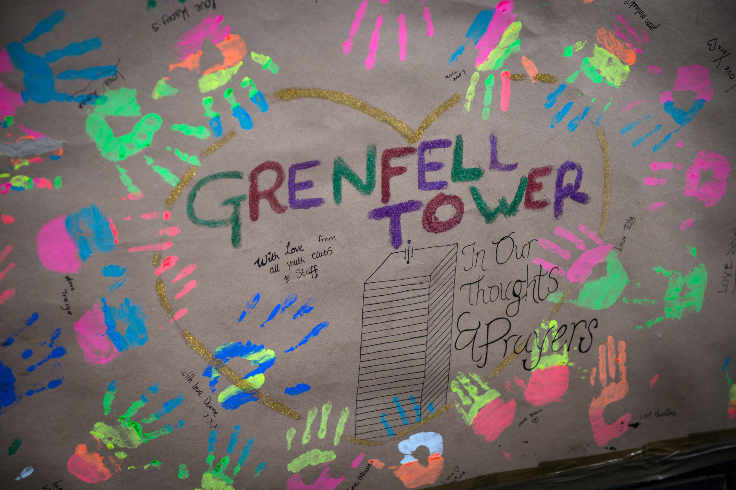 A handmade poster holds colourful handprints surrounding a golden-outlined heart, with Grenfell Tower and a hand drawing of the tower in the centre.