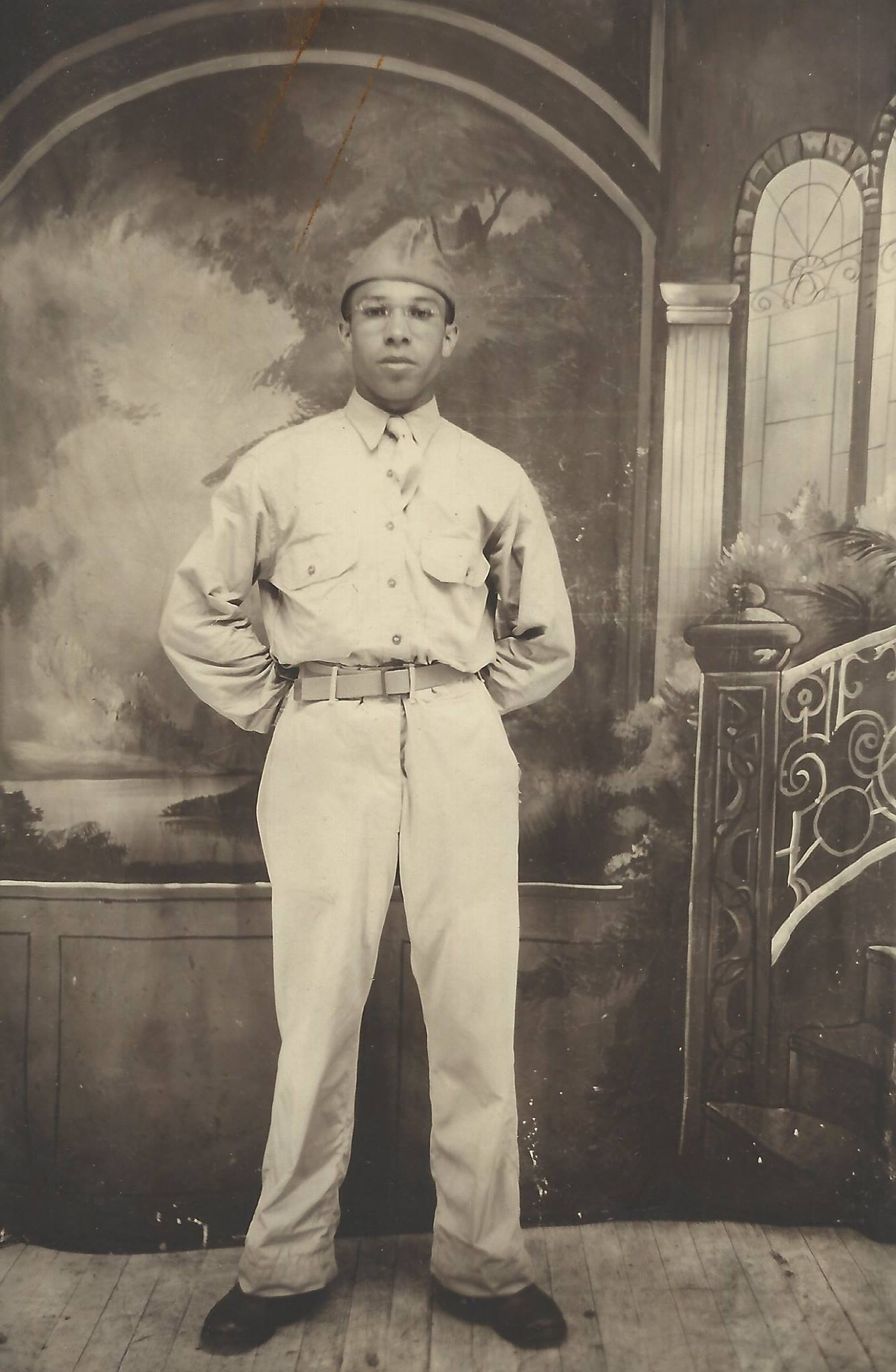 Three quarter length portrait of a Black G.I. proudly posing for the camera in military uniform with a photography studio backdrop.
