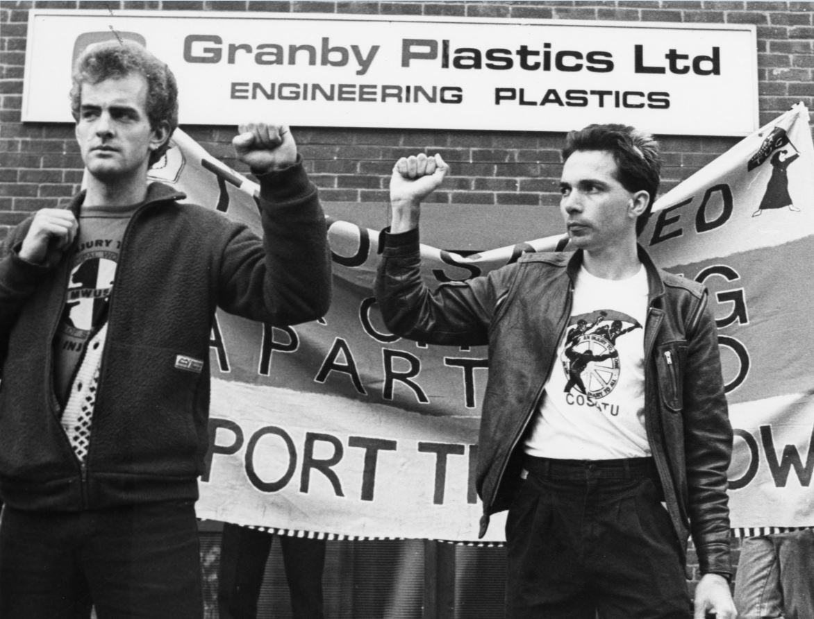 Two white men with raised fists are standing in front of a protest banner.