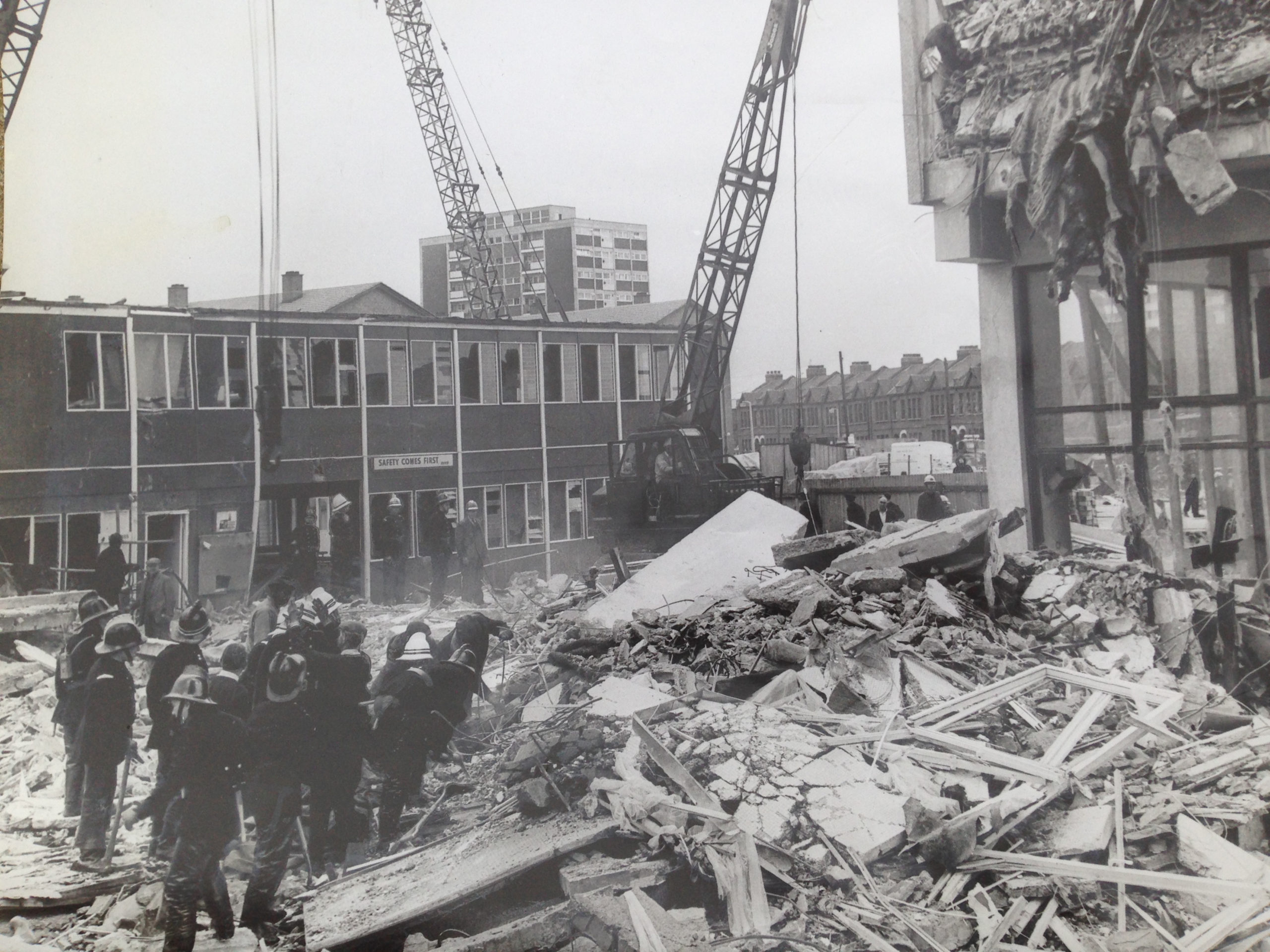 A huge pile of rubble lies in the foreground, with a small cluster of people close by to the left. Behind is a low brick building with two cranes overhead.