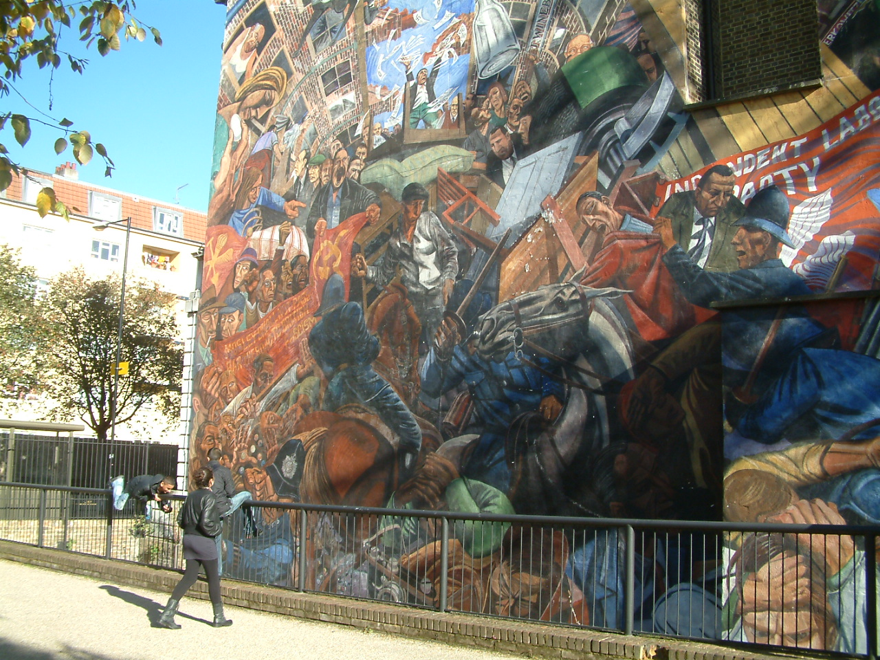 A section of the Cable Street mural showing the barricade and battles between mounted police and protesters. One child is looking up at the mural while another is playing.