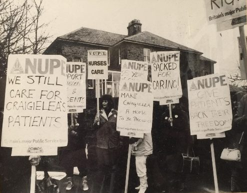 A black and white image of a group of people carrying homemade campaign banners. The roof of a house can be seen behind the group