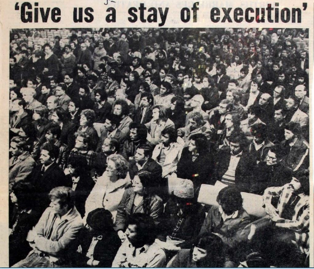 """A newspaper photograph of a crowd of Asian people seated in rows at a lobby with the headline """"Give us a stay of execution."""""""