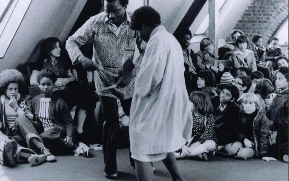 A Black man and woman dance in the middle of a room whilst a crowd of children sit on the floor watching them.