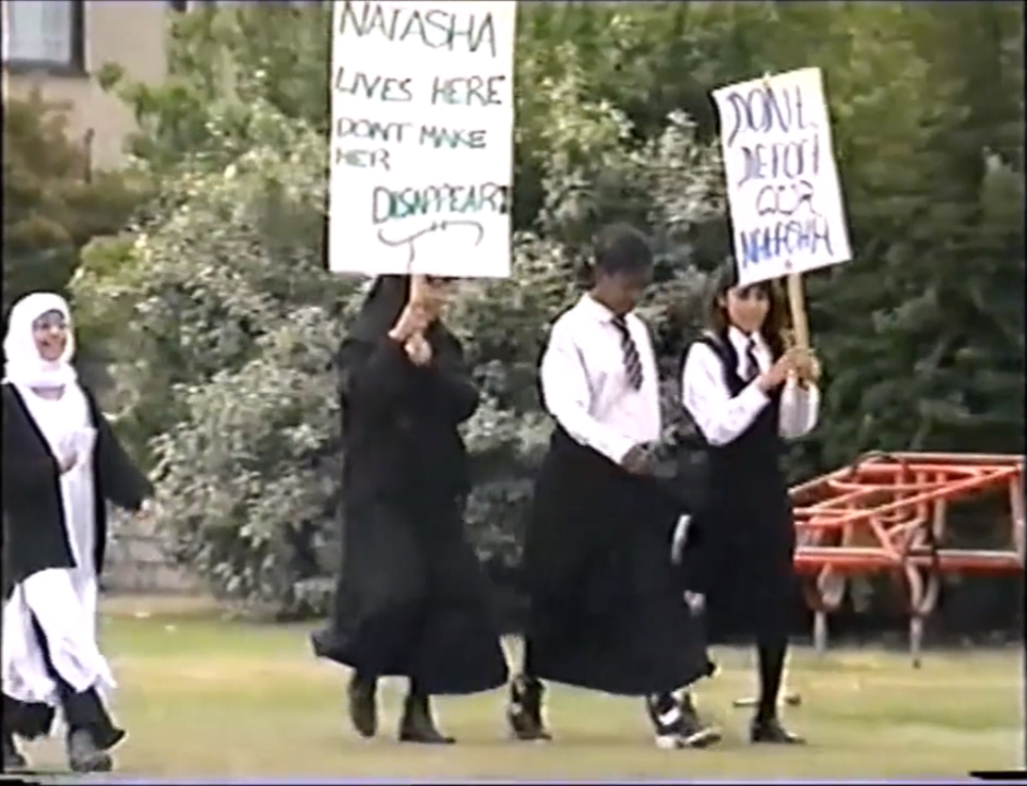 Four children in black and white school uniform walk on a lawn in front of green bushes. Two of the children carry protest banners on sticks above their heads.