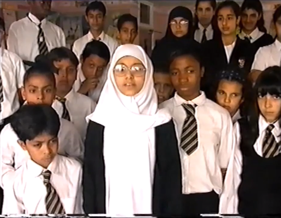 A group of students all wearing school uniform look at the camera. A girl wearing a white headscarf and glasses stands at the front.