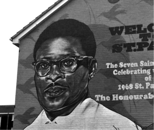 A black and white photograph showing a large painted mural on the side of a building. The mural features a portrait of Owen Henry.