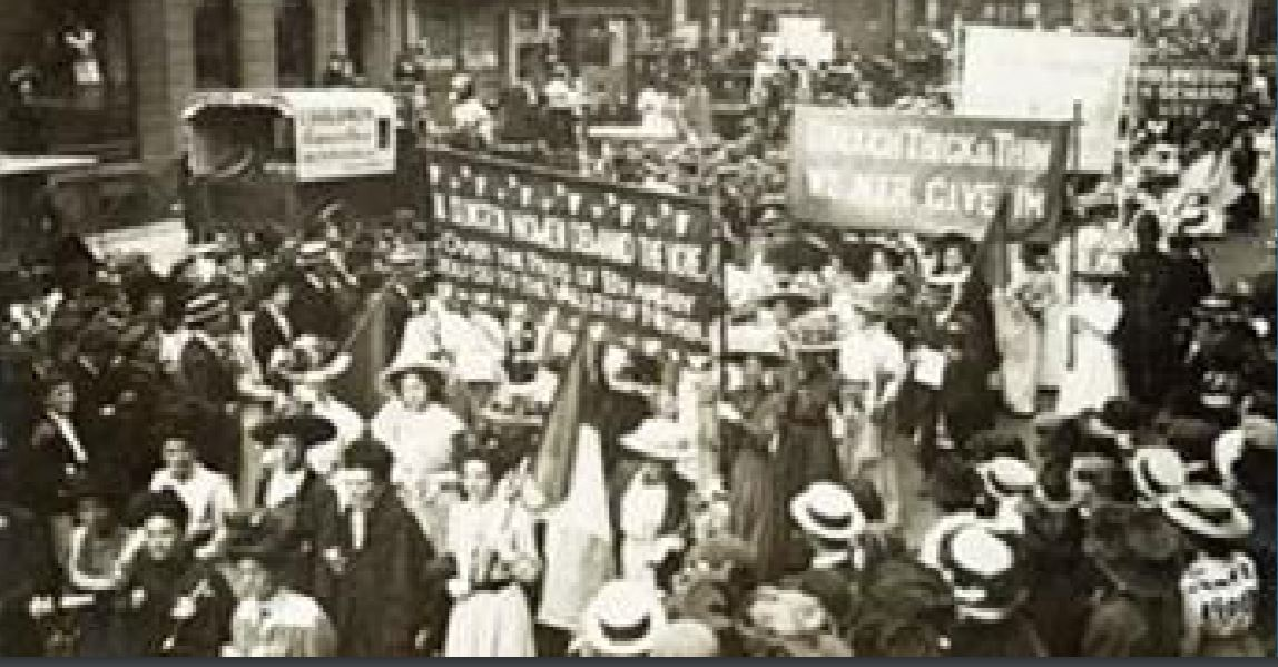 A crowd of suffragette women holding protest banners and flags march down a street watched by crowds of onlookers.