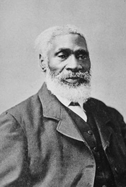 Black and white portrait photograph of Josiah Henson, seen with a white beard and wearing a suit.