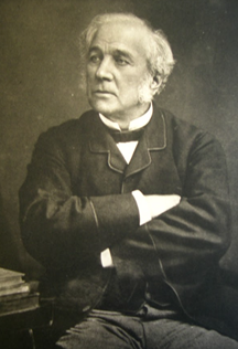 Black and white portrait photograph of Samuel Henson, seen with a white beard and wearing a suit with his arms crossed.