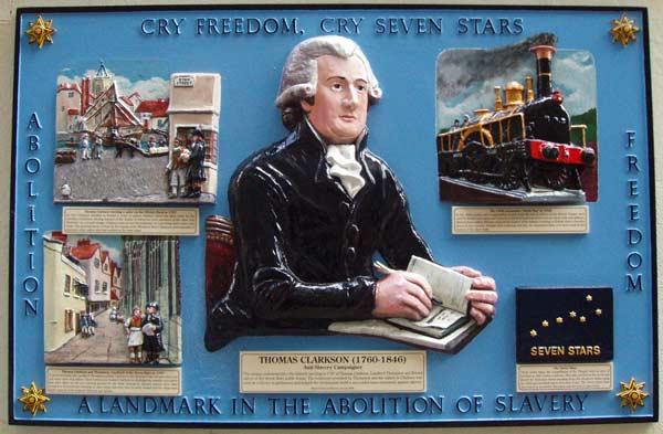 Photograph of a  plaque. Plaque shows Thomas Clarkson reading a book.