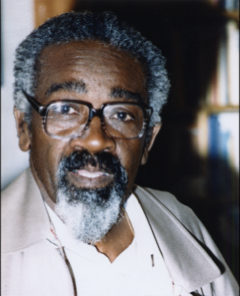 Photo of Oscar Abrams. A Black man with glasses, grey hair and beard, black moustache, wearing a casual white top and grey jacket.